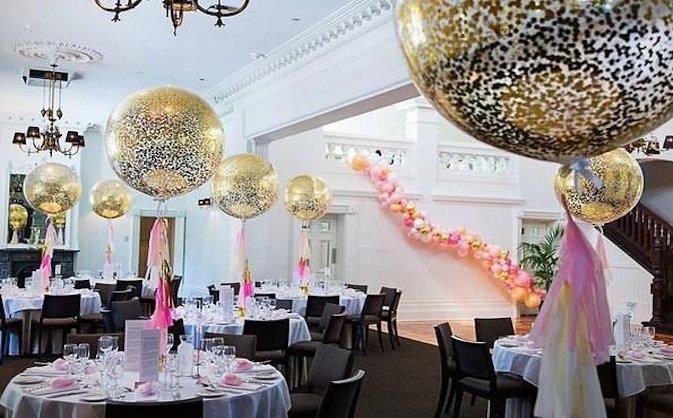 Зал украшен шарами и гирляндой в золотом и розовом цвете